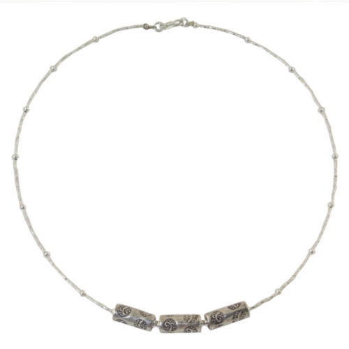 Three 950 silver amulets are engraved with motifs inspired by nature. Centering a necklace of diminutive silver beads, they adorn a necklace by Sasithon Saisuk.