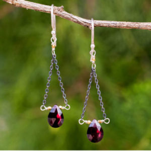 Garnet briolettes like rich red berries swing from dangle earrings that resemble the scales held by Lady Justice.