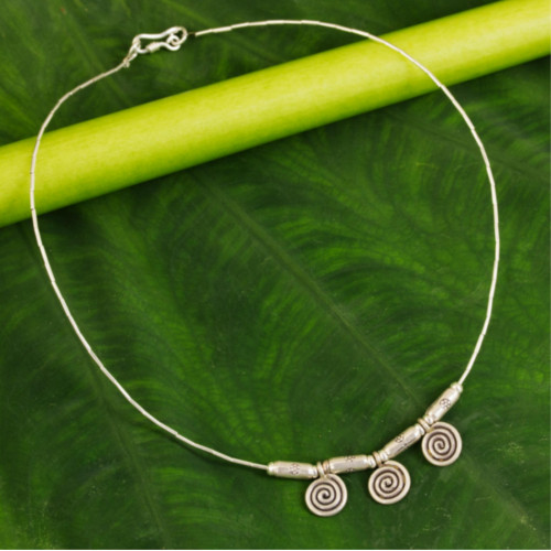 silver spirals engage the eye and mind. Sasithon Saisuk translates ancient Lanna (northern Thai) design motifs into contemporary jewelry. The pendants dangle from a silver chain, crafted by hand.