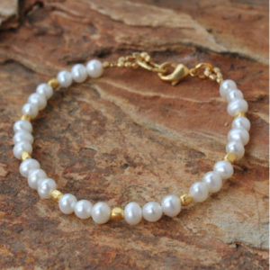 Freshwater pearls captivate with white iridescence in a bracelet designed by Khun Boom. The fabulous bracelet is crafted by hand with 24k gold plated brass accents.