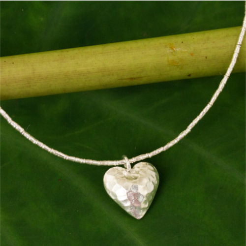 Fashioned of hammered 950 silver, a heart throbs with undying love. Sasithon Saisuk sets the charming pendant on a necklace of diminutive silver beads in the style of Thailand's hill tribes.